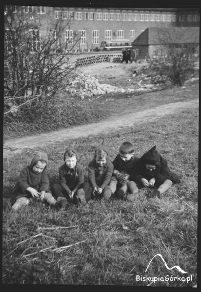 Dzieci siedzą przed Schroniskiem Młodzieżowym im. P. Benekego, 1940 r.