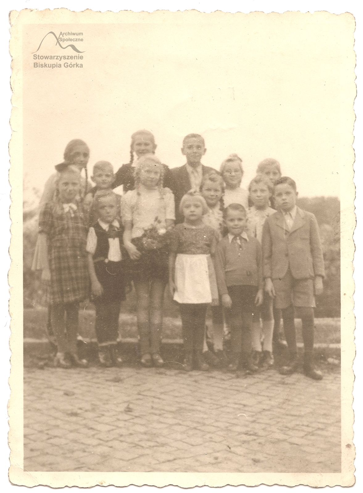 Urodziny Gizeli Olińskiej (z kwiatami), córki właścicieli Cafe Bischofshohe. Wsród gości Urszula Marschinke (Kiedrowska) z siostrą. Dzieci stoją przy ulicy prowadzącej do kawiarni. Zdjecie zrobiono w 1940 lub 1941 r.
